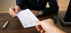 Picture of an HR representative handing a paper paycheck from PROWORK to an employee.